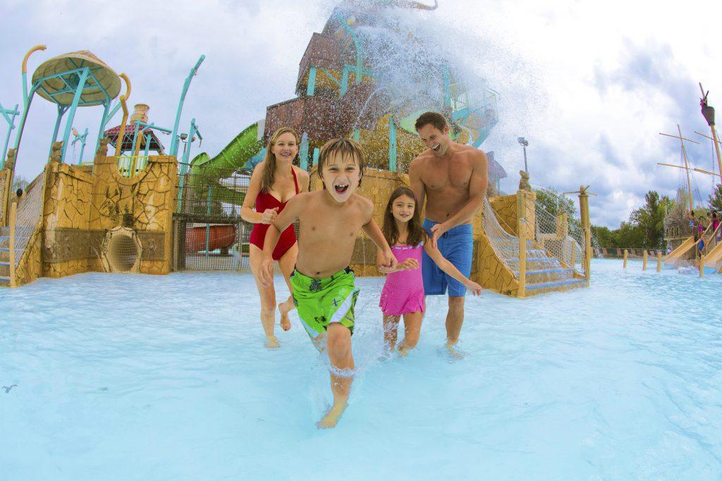 Family splashing through pool at waterpark